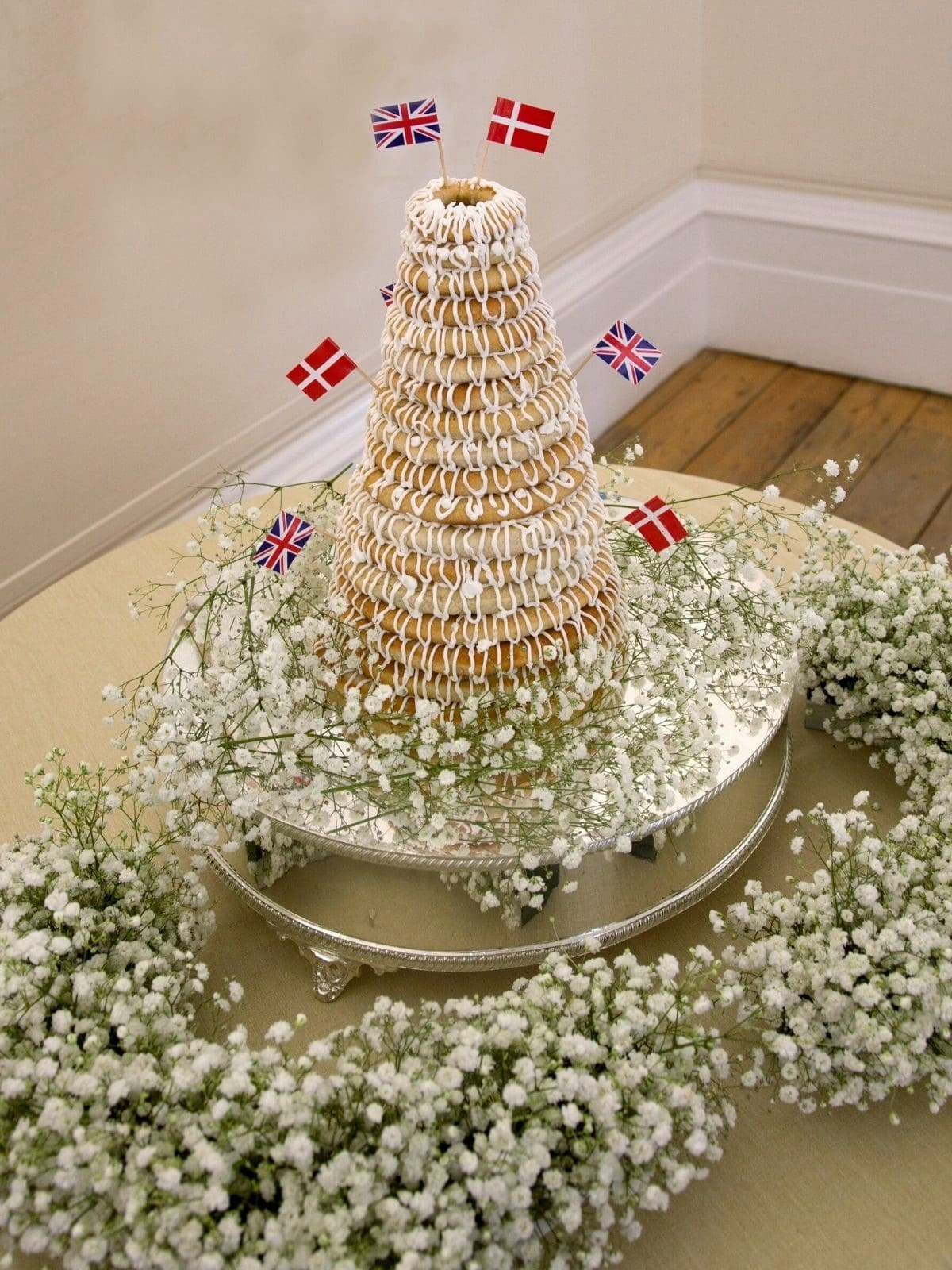 Danish Kransekage tower - marzipan wreath cake or ring cake - a recipe for a classic Danish cake.  Use it for weddings, Christmas, New Year, or any party that needs a fancy cake. Find recipes and inspiration @ danishthings.com Photo © Christina F. I. #DanishThings #kransekage # marzipanwreathcake #ringcake #Danish #tradition #weddingcake #NewYear #christmas #cake #party #classic #festive #tower