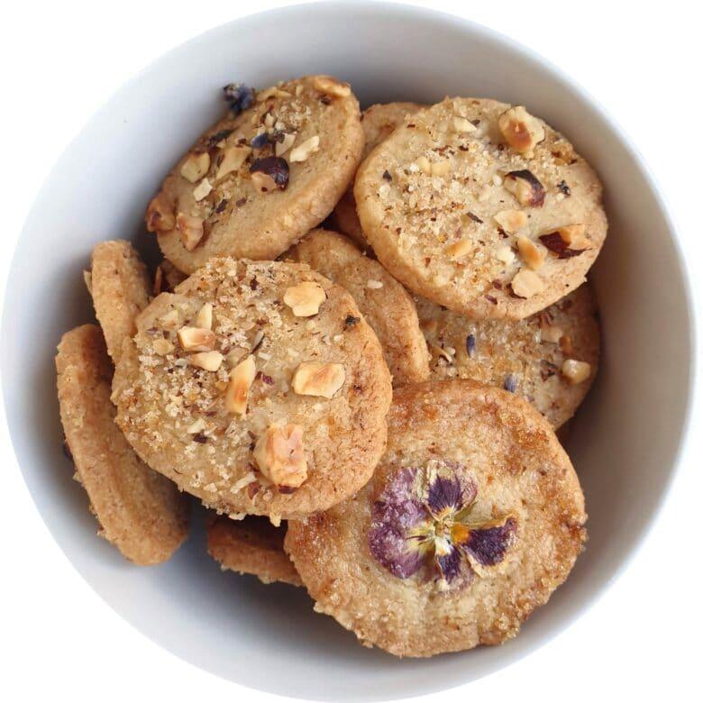 Sådan laver du lavendelsmåkager. Lav lækre sprøde småkager med en parfumeret lavendelsmag og et drys af nødder – eller vil du hellere dekorere med blomster? Find opskrifter, gratis print og inspiration til årets gang på danishthings.com #DanishThings #lavendel #småkager #cookies #lavendelsmåkager #spiselige-blomster #sommer #krydrede #parfumerede #smukke #smukmad #lækre #sprøde